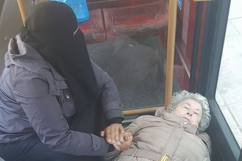 Touching picture shows woman in a niqab comforting elderly woman who fell down on bus